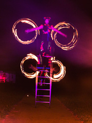 fire performance with free standing  ladder balance, performed by Luke Forrester of Will-o'-the-Wisp and the Great Australian Bite-sized circus